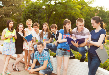 Group of students or teenagers with notebooks outdoors