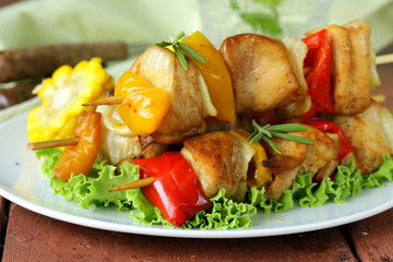 chicken kebabs with vegetables on wooden skewers