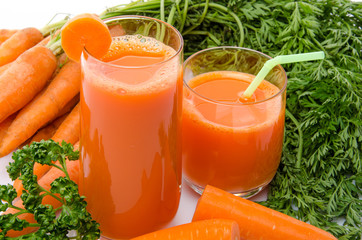 Composition with two glasses of carrot juice and carrots
