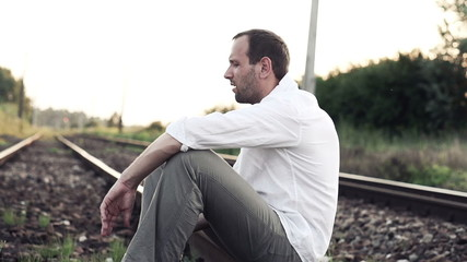 Sad, angry man sitting on railroad track