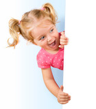 Smiling little girl looking behind a white board - 68031970