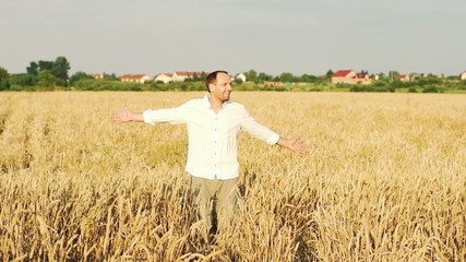 Happy man turning round on wheat field