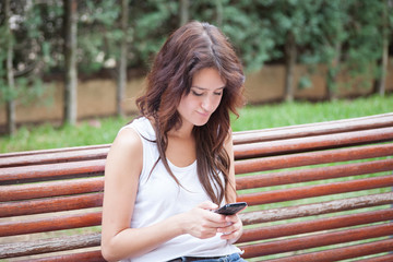Anxious girl writing text message with mobile phone.