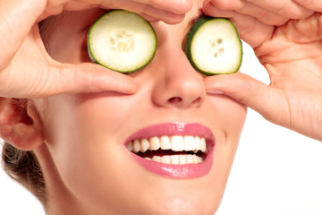 Young beautiflul smiling girl applying a cucumber beauty treatme