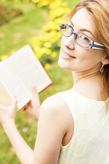 Portrait of a beautiful young woman reading a book in nature.
