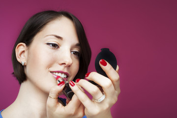 Beautiful young woman on pink background, putting on a make up.