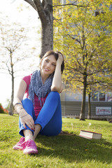 Beautiful young woman, sitting on grass, enjoying sunny day.