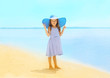 Fashion little girl in a striped dress and hat relaxing
