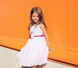 Fashion little girl posing in dress against colorful wall