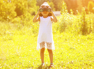 Positive child looks in binoculars in sunny summer day