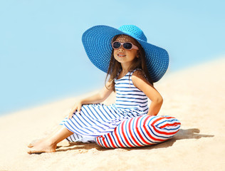 Pretty little girl in a striped dress and hat relaxing