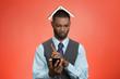 Displeased Man looking at smart phone, book over head