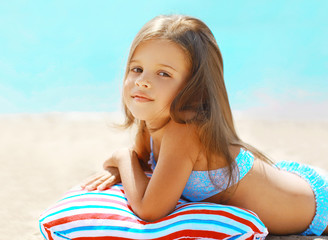 Summer vacation, little girl resting on the beach near sea
