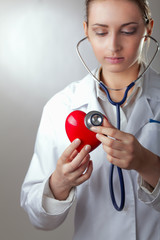 Doctor with stethoscope examining red heart, isolated on grey