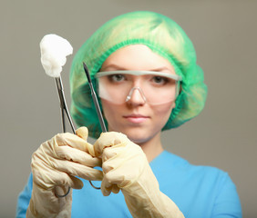Young woman doctor surgeon or nurse with scalpel