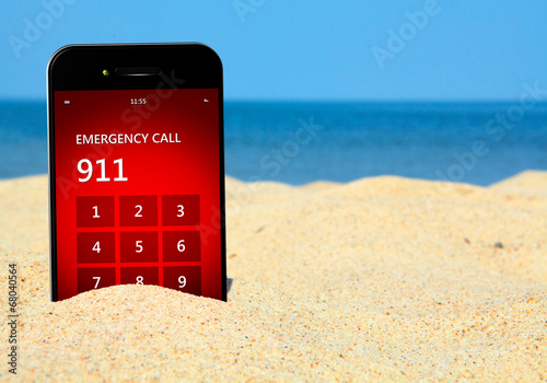 mobile phone with emergency number 911 on the beach - 68040564