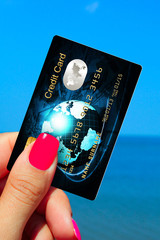 hand holding credit card on the beach