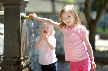 Two sisters playing with drinking water fountain