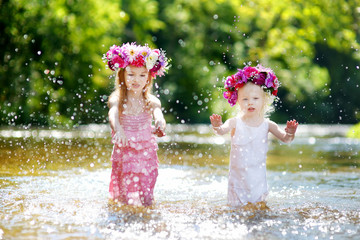 Two little sisters having fun by a river