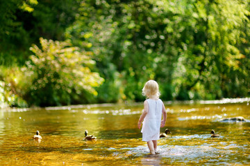 Cute toddler girl having fun by a river