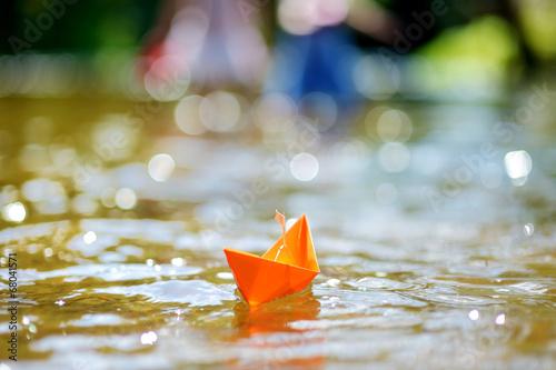 Leinwandbild Motiv Orange paper boat with a white flag