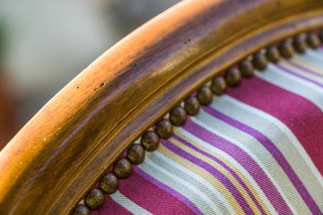 closeup of upholstery tacks on an old traditional wooden chair