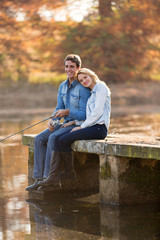 young man and girlfriend fishing on pier