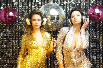 two beautiful sexy disco women in gold and silver catsuits danci