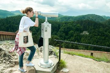 Cute young tourist girl watching landscape through binoculars