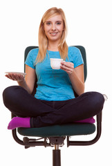 Beautiful girl relaxing in chair holds a cup of tea or coffee.