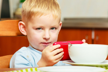 boy kid child eating corn flakes breakfast playing mobile phone