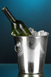 Bottle of wine in ice bucket on darck blue background