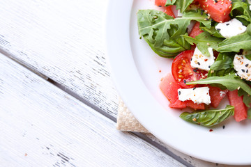 Salad with watermelon, feta, arugula and basil leaves