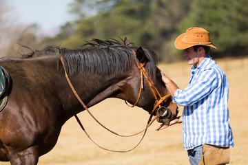 cowboy feeding his horse