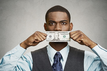 Bribery man with dollar bill on his mouth, grey wall background