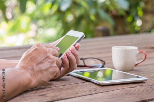 Leinwanddruck Bild Man hands touching smart phone with green tree background