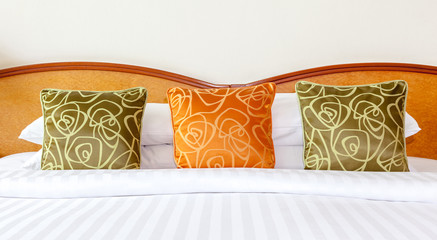 Hotel room setting with king sized bed, Thai silk orange and gre