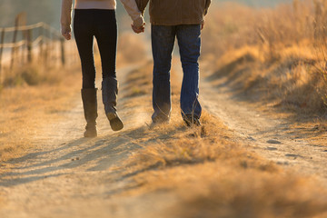 young couple holding hands walking on autumn path