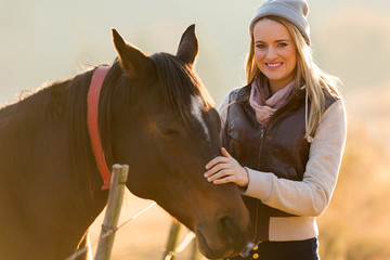 young woman petting horse