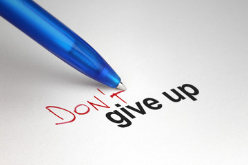 Don't give up. Written on white paper
