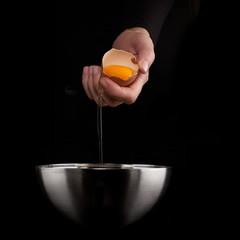 Hands breaking an egg.