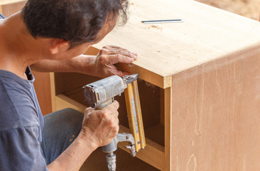 carpenter used air-gun for make new furniture