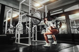 Fototapety Young sexy girl in the gym doing squat with barbell