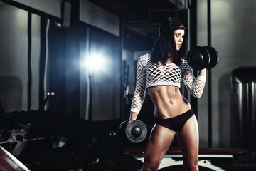 young fitness girl doing a workout with dumbbells in the gym