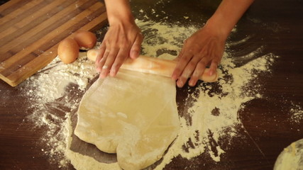Closeup of woman making dough at kitchen