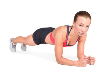 Young woman doing push ups. Isolated on white.