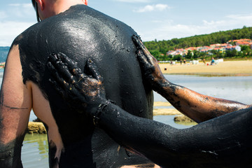 Man applying  healing clay to another man