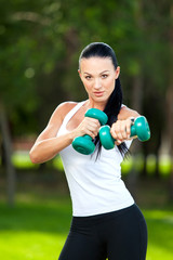 Portrait of woman  with dumbbell, outdoors