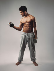 Muscular young man exercising with dumbbells