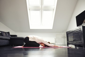 Young caucasian woman exercising yoga in living room